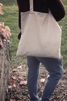 Modello del modello femminile della città della via con la borsa di eco di tela del tessuto di tote nella scena all'aperto di estate