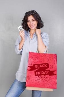 Modello del sacchetto della spesa della tenuta della donna con il concetto di venerdì nero