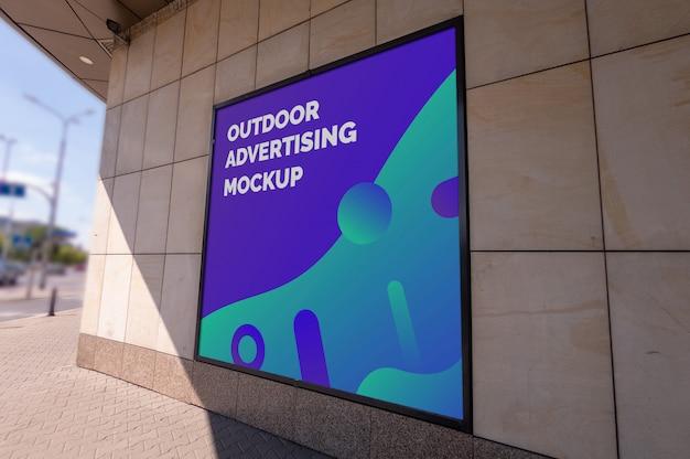Modello del tabellone per le affissioni quadrato di pubblicità all'aperto della città della via nella struttura nera sulla parete