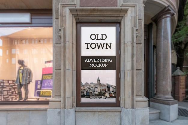 Modello del telaio pubblicitario classico all'aperto verticale nella vecchia finestra dell'edificio della città