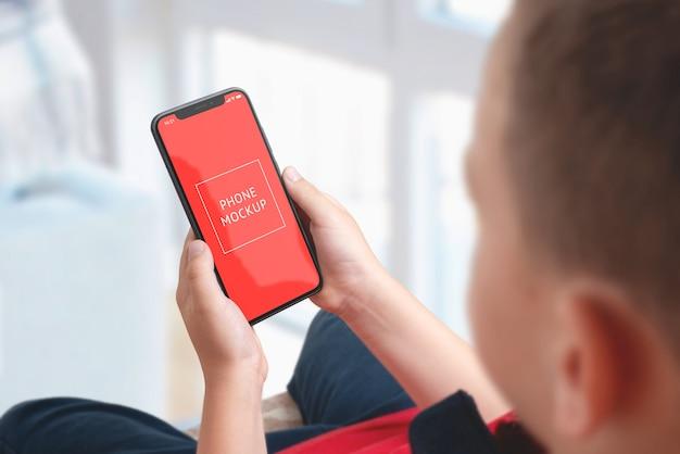 Modello del telefono in mani del ragazzo. vista sopra la spalla. schermata dell'oggetto intelligente per la presentazione dell'app. sfondo separato