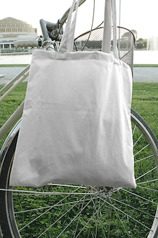 Modello della borsa di tela di eco del tessuto di tote della città della via che appende sulla bici nella scena all'aperto di estate