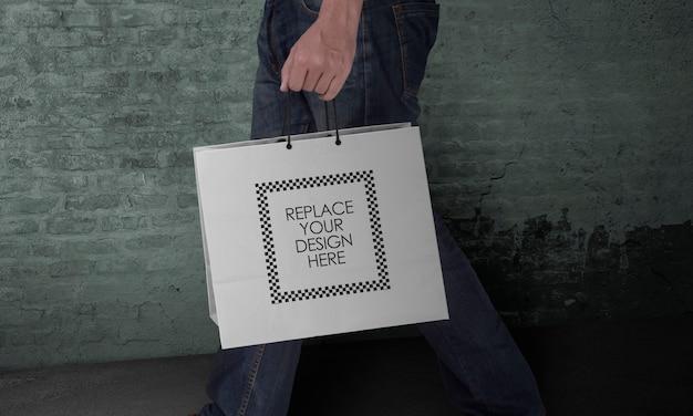 Modello della mano che tiene il sacchetto della spesa di carta