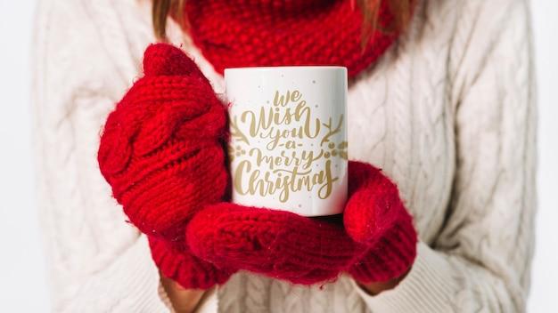 Modello della tazza della tenuta della donna con il concetto di natale