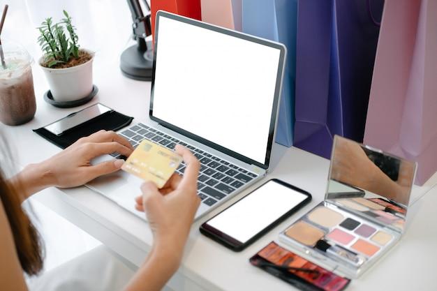 Modello di bella carta di credito della tenuta della donna che gode nel sito web di acquisto online con lo smartphone ed il computer portatile