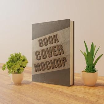Modello di copertina del libro sul tavolo di legno con piante di coppia