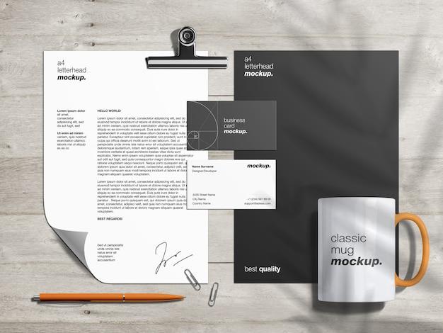 Modello di mockup di identità del marchio di cancelleria e creatore di scene con carta intestata, biglietti da visita e tazza classica