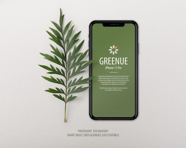 Modello di mockup schermo iphone con foglie della foresta