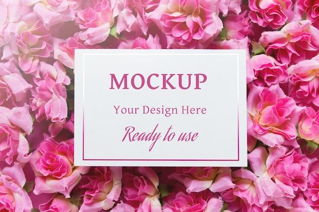 Modello di presentazione con carta bianca vuota bianca sulla superficie con rose fiori rosa.