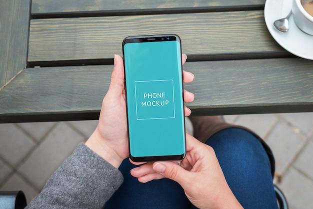 Modello moderno dello smart phone in primo piano delle mani della donna.