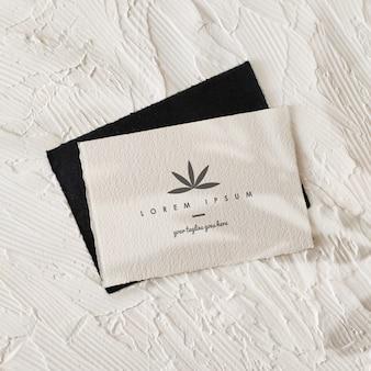 Modello realistico di logo di carta in bianco e nero con le ombre delle foglie