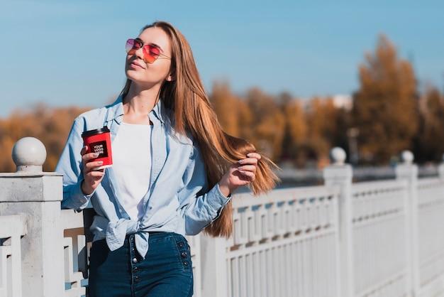 Modern blondemeisje die een kop van koffiemodel houden