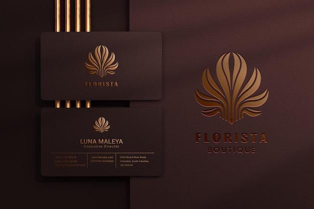 Modern logomodel met reliëf en ingeslagen effect op donker visitekaartje