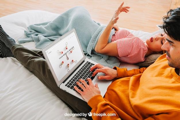 Modern paar met laptop in bed