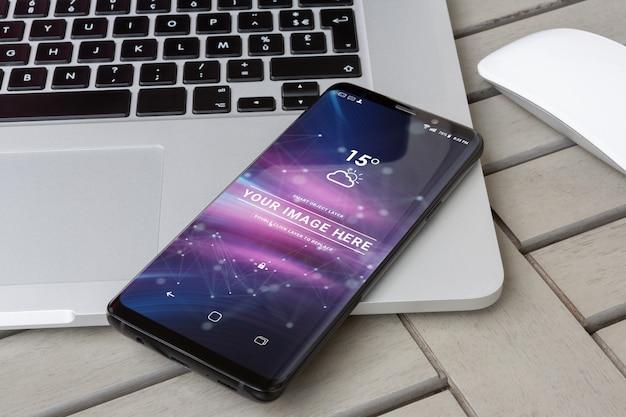 Moderne smartphone die op een laptop model legt