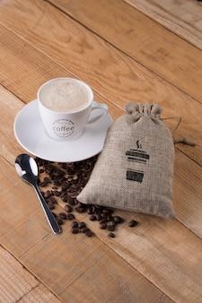 Mok met zak koffiebonen op tafel