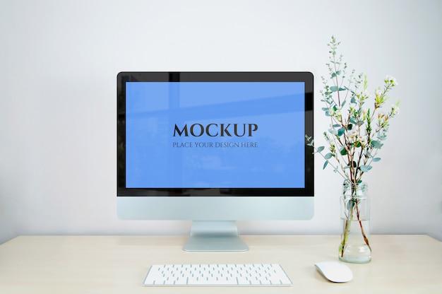 Monitor mockup, toetsenbord en computermuis met bloemenvaas.