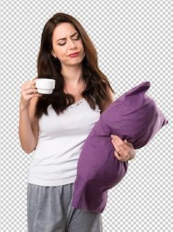 Mooi jong meisje met een hoofdkussen die een kop van koffie houden