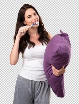 Mooi jong meisje met een hoofdkussen en met een tandenborstel