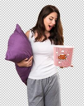 Mooi jong meisje met een popcorn van de hoofdkussenholding