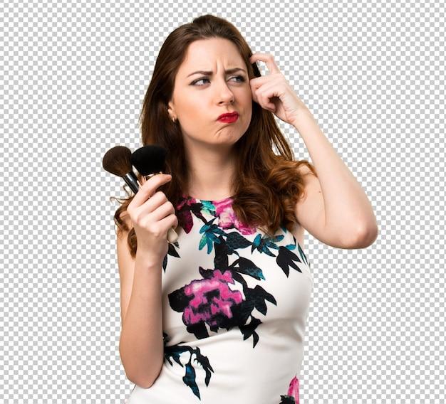 Mooi jong meisje met make-upborstel die twijfels hebben