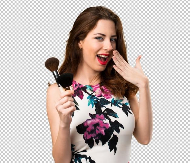 Mooi jong meisje met make-upborstel die verrassingsgebaar maken