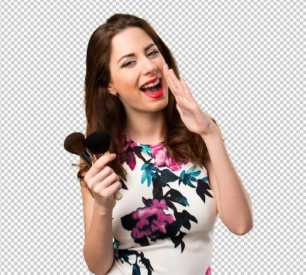 Mooi jong meisje met make-upborstel het schreeuwen