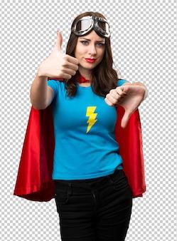 Mooi superheldmeisje dat goed-slecht teken maakt