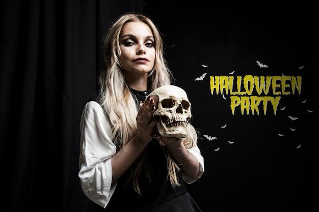 Mooie enge vrouw die met blonde haar een schedel houdt