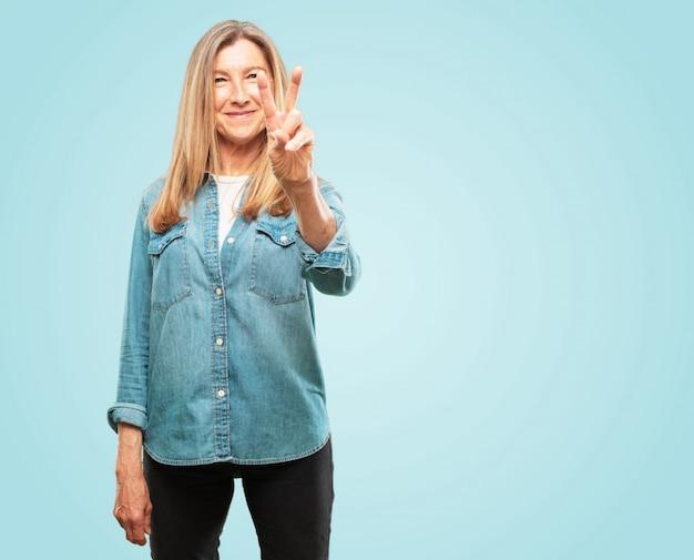 Mooie senior vrouw glimlachend en op zoek tevreden en gelukkig, tellen nummer twee met vingers