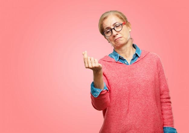 Mooie senior vrouw op zoek verdrietig en bezorgd, absoluut met lege handen, brak, in pure faillissement