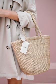 Mujer con un abrigo beige que lleva una bolsa de paja con una maqueta de etiqueta de marca