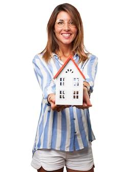 Mujer alegre con la casa de sus sueños