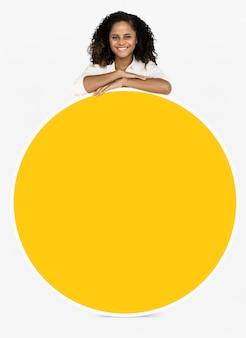 Mujer alegre mostrando una tabla redonda