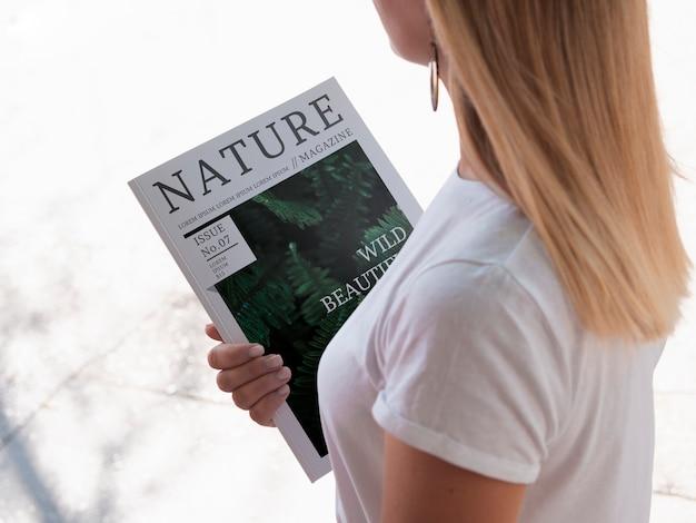 Mujer de alto ángulo sosteniendo una revista simulacro