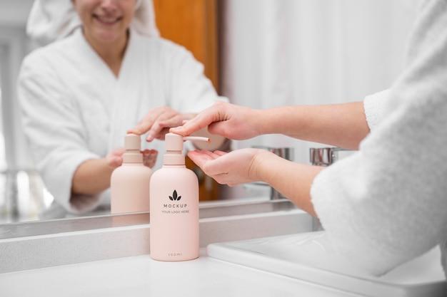 Mujer aplicar crema hidratante en casa después de una ducha