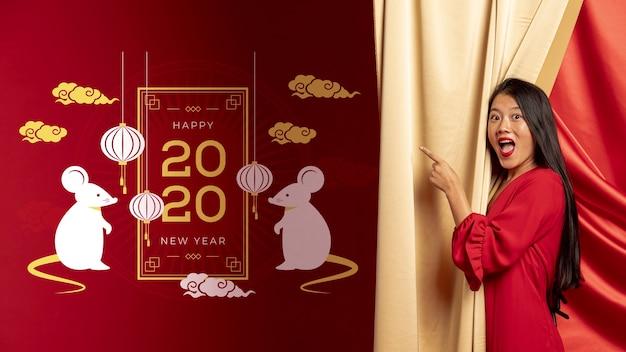 Mujer apuntando a la decoración con fecha de año nuevo