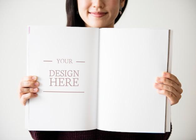 Una mujer asiática está sosteniendo una revista en blanco