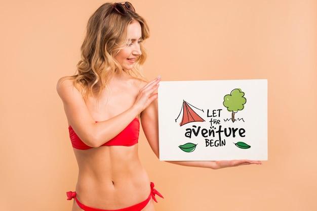 Mujer atractiva en bikini presentando mockup de cover