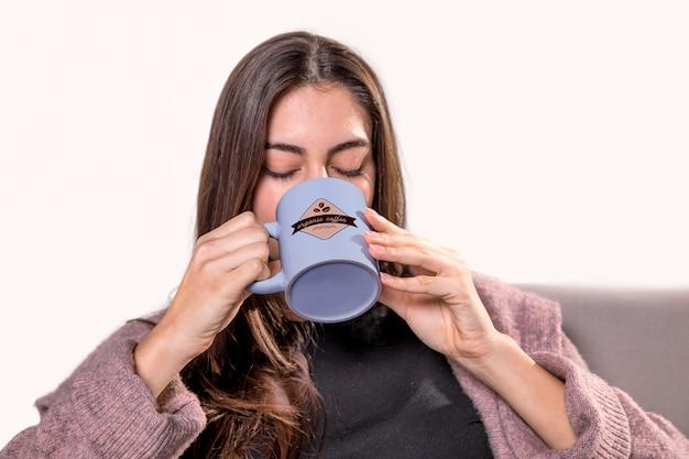 Mujer bebiendo de la taza azul