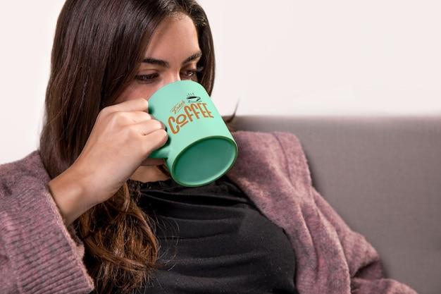 Mujer bebiendo de la taza verde