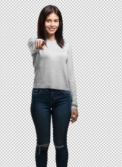 Mujer bonita joven alegre y sonriente apuntando hacia el frente