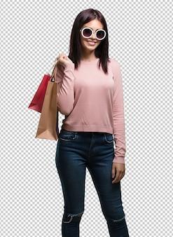 Mujer bonita joven alegre y sonriente, muy emocionada llevando una bolsa de compras, lista para ir de compras y buscar nuevas ofertas