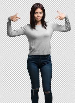 Mujer bonita joven orgullosa y confiada, señalando con el dedo, ejemplo a seguir, concepto de satisfacción, arrogancia y salud