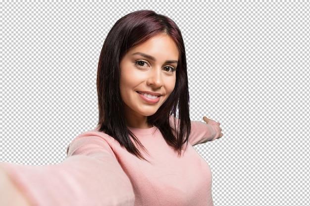 Mujer bonita joven que sonríe y feliz, tomando un selfie, sosteniendo la cámara