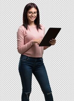 Mujer bonita joven sonriente y confiada, sosteniendo una tableta, usándola para navegar por internet y ver las redes sociales, el concepto de comunicación