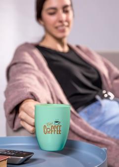 Mujer borrosa con taza de café verde