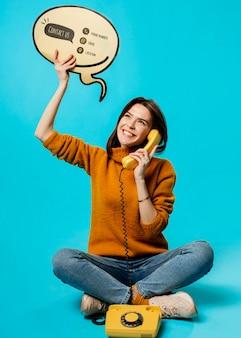 Mujer con burbuja de chat y teléfono antiguo