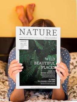 Mujer en la cama mostrando una revista de naturaleza