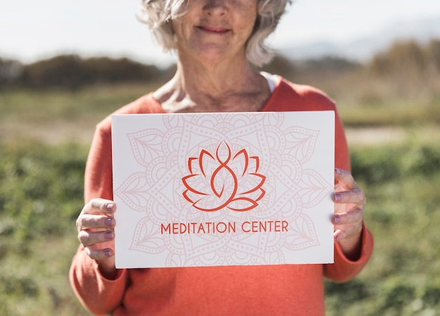 Mujer con un cartel de logotipo del centro de meditación